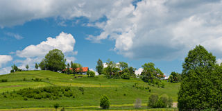 Green hill with bushes trees and house Royalty Free Stock Image