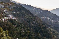 Green hill near Kangchenjunga mountain with clouds above, trees and village with sunlight that view in the evening in North Sikkim Royalty Free Stock Images