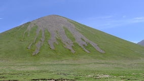 Green hill with a palmated, barren and rocky summit on Tibetan Plateau Royalty Free Stock Photos