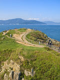 Green hill by sea with people walking along paths Stock Image