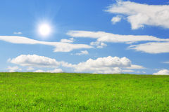 Green hill under blue cloudy sky whit sun Stock Images