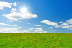 Green hill under blue cloudy sky whit sun Royalty Free Stock Photos