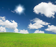 Green hill under blue cloudy sky whit sun Stock Photos
