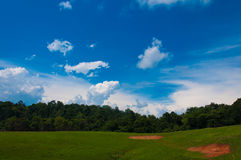 Green hill under a blue sky. Royalty Free Stock Images