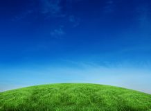 Green hill under blue sky Royalty Free Stock Images