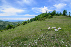 Green hill under blue sky with white clouds. Beautiful summer landscape. Nature of Georgia Royalty Free Stock Image
