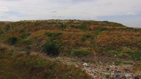 Behind the hill garbage dump. After a green hill, a view of an unauthorized garbage dump opens up stock footage