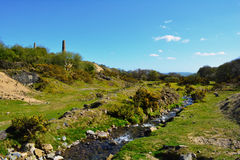 Green hill and a water stream in Bodmin Moor area near old mining shaft Royalty Free Stock Image