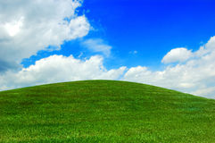 Green Hillock Blue Sky White Clouds. Natural background of green hill, blue sky and white coulds Royalty Free Stock Photography