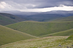 Green hills below storm clouds Stock Image