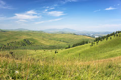 Green Hills Covered by Trees and Blue Sky with White Clouds Royalty Free Stock Photography