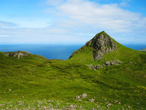 Green hills of the Isle of Skye. Green rocky hills on the Isle of Skye in Scotland with blue ocean in the background Royalty Free Stock Photo