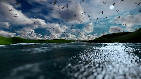 Green hills and lake with seagulls flying, beautiful afternoon clouds stock footage
