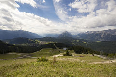 Green hills with mountains in the back. Green hills and a village with mountains in the back Royalty Free Stock Image