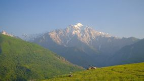 Green hills and snow mountain landscape. On the sunny day stock video