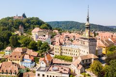 Green hills, spires and red tiled roofs of Walled old town of Sighisoara, Transylvania, Romania. stock images