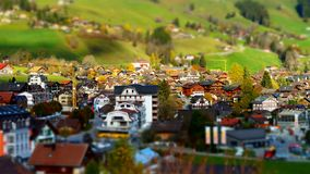 Green hills in swiss valley tilt shift view, sunny day. Chateau-dOex, Switzerland royalty free stock photo
