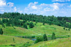 Green hills and trees on blue sky background Stock Photography