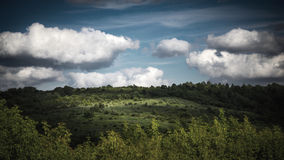 Green hills  under the cloudy sky. Horizontal Royalty Free Stock Photo