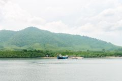 Green hilly tropical island with  blue ferry in the sea. Green hilly tropical island in cloudy day with small jetty and blue ferry in the sea Stock Photography
