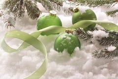 Green holiday balls in snow Stock Photos