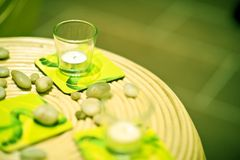 Green Home Decoration. Wattle Table, Small Glass Candles and Some Rocks Stock Images