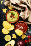 Green Homemade Guacamole with Tortilla Chips and Salsa. On dark rustic background Stock Photos