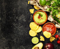 Green Homemade Guacamole with Tortilla Chips and Salsa. On dark rustic background Stock Image
