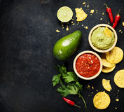 Green Homemade Guacamole with Tortilla Chips and Salsa. Mexican food concept: tortilla chips, guacamole, salsa and fresh ingredients over vintage rusty metal Stock Images