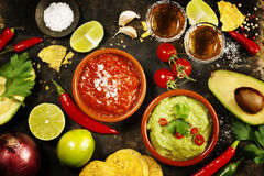 Green Homemade Guacamole with Tortilla Chips, Salsa and tequila. Mexican food concept: tortilla chips, guacamole, salsa, tequila shots and fresh ingredients over Stock Photos