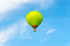 Green hot air balloon in flight. Against the blue sky and clouds Royalty Free Stock Image