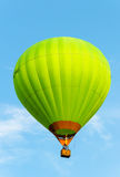 Green hot air balloon in flight against the blue sky. Stock Photos