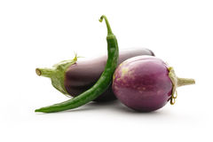 Green hot chilly pepper with two eggplants Stock Images