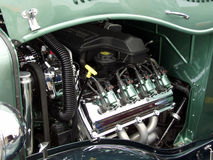 Green Hot Rod Engine. Fills the frame. Hood at the top of frame creates interesting line. Engine parts create repitition stock photos