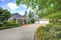Green house with beautiful curb appeal. View of three car garage and driveway Stock Images