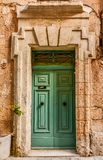 Green House door in Malta. House entrance door in Malta, painted in typical strong colors Royalty Free Stock Image