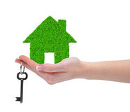Green house with key in hand. Isolated on white Royalty Free Stock Photos