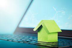 Green house on keyboard and wind power plants on computer screen. Smart house, ecology power, real estate, renewable energy concep. T royalty free stock photography