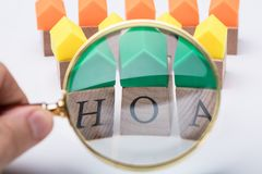 Person`s Hand Examining Homeowner Association Wooden Blocks. Green House Model Over Homeowner Association Wooden Blocks Seen Through A Person Holding Magnifying stock images