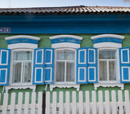 Green House Windows with Blue Shutters Stock Photos