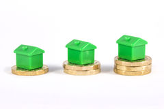 Green Houses Sitting on Top of Coins. Green Houses sitting on top of stacks of coins, over a white background Royalty Free Stock Images