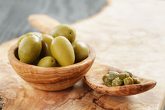 Green huge olives and capers on wood table Stock Photo