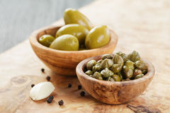 Green huge olives and capers on wood table Royalty Free Stock Photography
