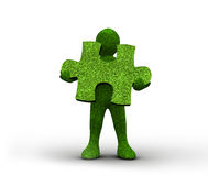 Green human representation holding a grass jigsaw puzzle Stock Photo