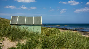 Green Hut by the Sea. A green beach hut hiding in the grass and sand dunes on the Northumberland coast line Stock Photography