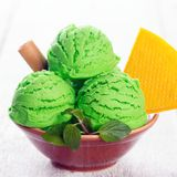 Green ice cream. Scoop of green ice cream in bowl on wooden background royalty free stock photo
