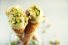 Green ice cream in waffle cone with chocolate and pistachio nuts on grey stone background. Summer food concept, copy. Space. Healthy gluten free ice-cream royalty free stock images