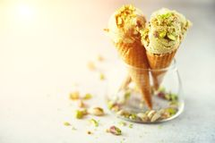 Green ice cream in waffle cone with chocolate and pistachio nuts on grey stone background. Summer food concept, copy. Space. Healthy gluten free ice-cream royalty free stock image