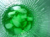 Green Ice Drink. Macro photo of ice and green drink in textured glass Stock Photo
