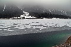 Green ice lake. View of a beautiful lake covered with ice, but also able to see clear water during the way from Germany to Austria in winter Royalty Free Stock Images